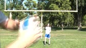 Girl throws football right at camera while adult hands catch, in sunlight with yellow field goal post behind her.