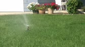 oxigênio : Sprinkler is watering green lawn in summer with head rotating 180 degrees.