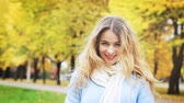 Young Fashion Woman Throwing Leaves Up in Autumn Park. Smiling Happy Female Looking at Camera. Warm Colors Toned Video with Copyspace. Stock Footage