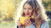 Young Woman with a Mug of Hot Tea in Hands on Autumn Background. Smiling Happy Female Drinking Hot Beverage in Sunny and Windy Day. Beautiful Girl Close-Up Portrait. Warm Colors Toned Video.