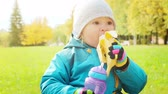 Child Eating Banana and Drinking Water in Autumn Park at Sunny Day. Kid Outdoors in Fall. Nature Background. Warm Colors Toned Candid Video. Handheld Camera.