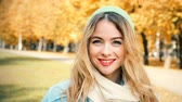 Young Fashion Hipster Girl in Sunny Autumn Day. Candid Smiling Happy Female Looking at Camera. Close-Up Trendy Casual Woman Portrait. Wind Waving Her Hair. Tree in Fall Background. Toned Footage. Stock Footage