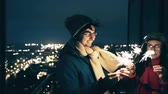 Smiling Young Couple Outdoors with Sparklers in Winter. Happy Man and Woman Celebrating New Year or Christmas with Bengal Lights at Night. Evening City Lights Bokeh Background.