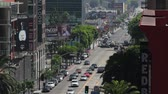 telephoto lens : Long shot looking South on Vine Street towards Hollywood Boulevard in Los Angeles, California. Visible off in the distance is vehicle and pedestrian traffic. Stock Footage