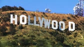 кинозвезды : Close view of the Hollywood sign in Los Angeles with plant life in the foreground blowing in the wind.
