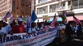 cartão : People Marching at Immigration Rally. Hundreds of people young and old march while waving picket signs and American flags in the air using noise makers and cheer during an immigration rally in downtown Los Angeles on September 22 2013.