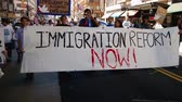 конгресс : Immigration Reform Banner. A large white picket banner that reads Immigration Reform Now is held up and carried by multiple people during an immigration rally in downtown Los Angeles on September 22 2013.