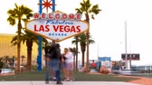 pecado : Timelapse wide shot of the world famous Welcome to Fabulous Las Vegas Nevada sign with tourists walking around and in front of the landmark posing for pictures with traffic passing by in the background. Designed in the MidCentury modern architecture sty Vídeos
