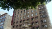 tomada : Cecil Hotel Wide. Three-quarter wide shot of the Cecil Hotel as the camera tilts up to the building with a tree in the foreground and back down. Built in the 1920s, the Cecil Hotel in Downtown Los Angeles has become known for criminal activity including s Stock Footage