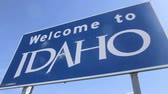 Welcome To Idaho Sign, Pan. Low angle pan to and from a blue Welcome To Idaho sign placed along the highway.