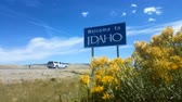 Welcome To Idaho Sign, Wide. Wide angle static shot of a blue Welcome To Idaho sign placed along the highway.