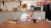 knocking : Cute baby chef preparing to cook on a kitchen table covered with flour. Little boy rearranges the form for cookies