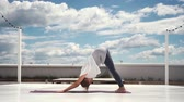 пилатес : Flexible woman does yoga in slow motion in background of white clouds and bright blue sky. Girl changes yoga pose. Downward facing dog pose - Adho Mukha Svanasana. One Legged Down Dog pose Стоковые видеозаписи
