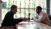 Two young men are discussing startup sitting at table in cafe. Businessman shares ideas, talks, discusses new projects with his colleague sitting near a cafe window