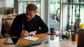 Young handsome man writes in notebook and works on tablet in cozy cafe interior. Attractive young businessman is writing in notepad. Shot in slow motion