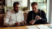 Portrait of two cheerful businessmen discussing project using tablet computer and cell in cozy cafe. Shot in slow motion