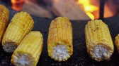 Cooking corn on grill close-up. Corn lies in the background of a strong fire. Shot in slow motion