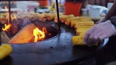 Cooking corn on grill close-up. Corn lies in the background of a strong fire. Man turns over corn so it doesnt burn on the grill. Shot in slow motion