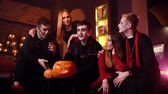 Young man in festive priest costume hugs his girlfriend at Halloween meeting of friends in cafe. Guy in the image of Count Dracula tells stories. Holiday carved pumpkin on table. Shot in slow motion