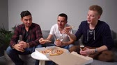 Group of young friends eating pizza taking it from table. Guys are holding beer bottles in their hands.