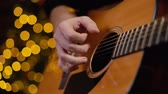 Man plays guitar close-up. Shooting in slow motion. Against the background of a decorated Christmas tree with a bokeh effect.