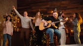 Cheerful young friends are dancing and singing at the New Year party in cozy house. Happy young man plays guitar. Christmas tree with garland and wall with festive illumination in background