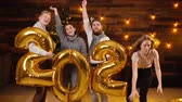 Two attractive guys and two beautiful girls are holding inflatable foil numerals 2020. Group of friends are celebrating New Year. Girl drops an inflatable air number
