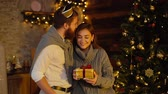 Young man gives New Year present to his girlfriend by the Christmas tree. Girl with smile accepts gift from her husband. Couple is hugging on New Year Eve. Guy kisses his girlfriend on the forehead. Archivo de Video