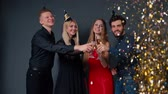 Group of cheerful young people are clinking with champagne glasses. On friends from above the festive confetti falling. Shooting in slow motion in professional studio on isolated dark background.