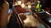 capitais : Bangkok, Thailand - May 3, 2018 : Unidentified man sells street exotic food. Dried insects, bugs, worms, scorpions and frogs at Yaowarat Road in Bangkoks Chinatown district