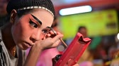 pequim : Bangkok, Thailand - October 2, 2019 : Chinese opera performer prepares for a show and applies paint to turn his face into a mask Stock Footage