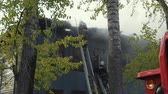 bombeiro : Firefighters extinguish the fire. Burning old abandoned house. Slow Motion Video Stock Footage