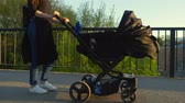 kinderwagen : A girl with a black stroller walks through the city, sunny day