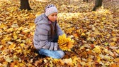 tosses : nice teen girl sits squatted and holds yellow leaves in beautiful autumn city park, then tosses up it Stock Footage