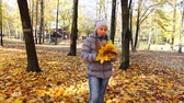 tosses : nice teen girl stands with yellow leaves in beautiful autumn city park, then tosses up it and goes away