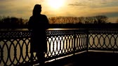 inclinar : silhouette of pretty lady that lean on railings near clear lake, sunset