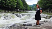 freshness : pretty woman stands in front of small waterfall at mountains Carpathians