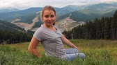 loiro : young smiling girl sits back on really green grass in mountains and turns around