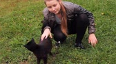 female : young girl has rest in village and plays with nice black cat