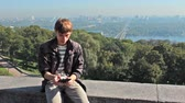 eğitim : young man reading on electronic book, behind him very nice view of capital city, Kiev Ukraine
