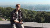 loiro : young man reads electronic book, on background nice view of capital city, Kiev Ukraine