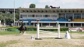 mounted : KIEV, UKRAINE - JUNE 9: Jockey on horseback professionally jumps over the barrier in the competitions at the Kiev Hippodrome on June 9, 2013 in Kiev, Ukraine. Kiev hippodrome was built in 1962-1969 Stock Footage
