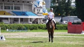 equitation : KYIV, UKRAINE - JUNE 9: Beautiful woman riding a horse in Kyiv, Ukraine. Hippodrome on June 9, 2013 in Kyiv, Ukraine. Horse riding promotes the comprehensive development of the human body. Stock Footage