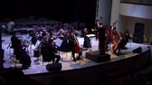 instruments vent : DNIPRO, UKRAINE - JANUARY 14, 2018: Cellist Artem Poludeny and Academic Symphony Orchestra - main conductor Ivan Cherednichenko perform Concert by Carl Philippe Emanuel Bach for cello with orchestra in a minor at the Philharmonic.