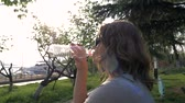 Pretty young girl drinking water from plastic bottle outdoor in park, against sunlight