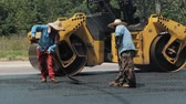 urban renewal : 19 August 2018. Suzhou, China. Workers making asphalt with shovels at road construction Stock Footage