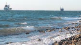 The waves crashing against the rock on the sea shore, cargo ship on the background Стоковые видеозаписи