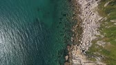 view from above : Aerial shot of mountain cliff and blue sea water. Rocky cliff and blue water in sea bay aerial landscape from above.