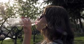 hot water : Pretty young girl drinking water from plastic bottle outdoor in park Stock Footage