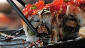 鮭 : Close-up of chopsticks holds sushi roll over a plate in restaraunt. Traditional Japanese cuisine.